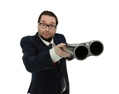Comedian Gary Delaney wearing a suit and holding a rifle against a white background