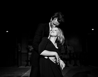 A man and a woman smile and embrace against a dark background.
