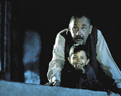 A young boy and an old man look down from a balcony.