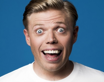 A photo of Rob Beckett with a comically wide smile and wide eyes
