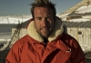 Ben Fogle, a man with blonde hair, stands in the snow wearing a large red parka