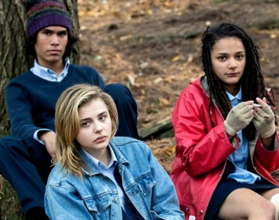 Three teenagers sit in a wood and look directly into the camera
