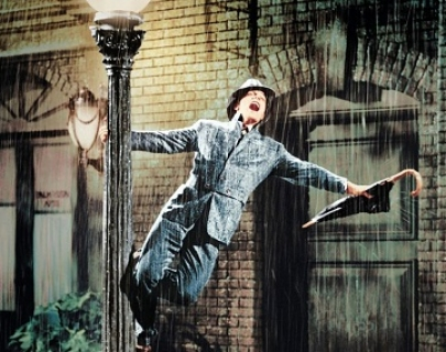 Gene Kelly, in a raincoat and a hat, swings around a lamp post in the rain