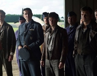 A group of men in World War Two flight suits stand in an aircraft hanger