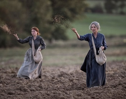 Two women in period dresses spread seeds over a field