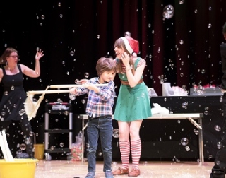 A woman in a green dress and a santas hat, and a young boy, are surrounded by bubbles on a stage