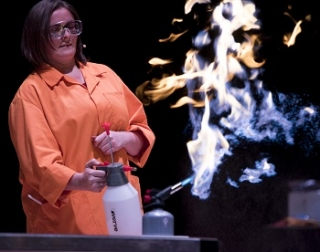 A woman in a white lab coat using a small flame thrower