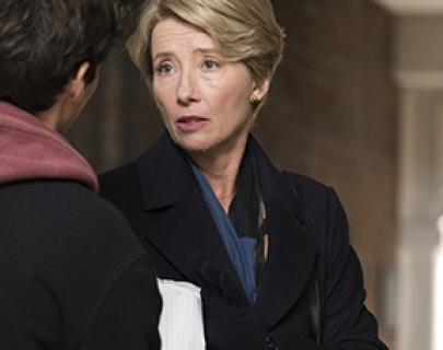 Actress Emma Thompson wears a black coat and blue scarf and talks to a boy in a hoodie.