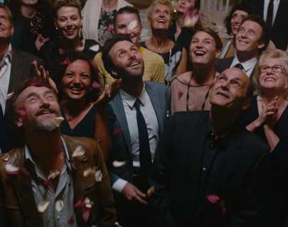A group of people smile whilst looking up to a shower of flower petals.