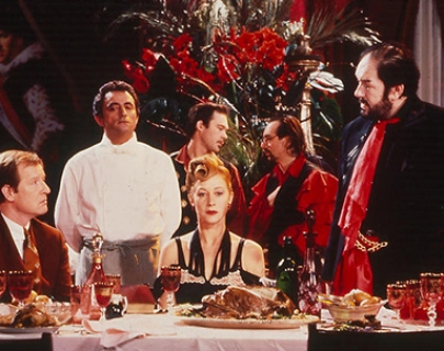 A woman sits at the centre of a banquet table surrounded by four men in suits and a man in a chef's uniform.