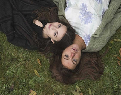 A mother and her daughter lying on the grass looking at the sky