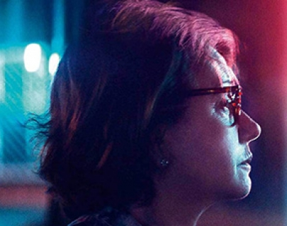 A woman wearing glasses is lit by blue and red light