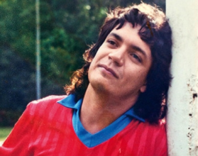 A young man in a red and blue football shirt leans against a goalpost