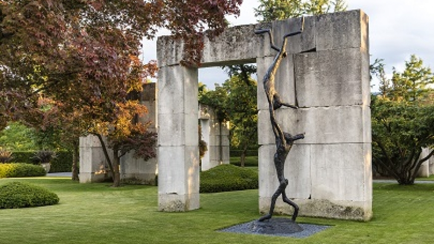 Barry Flanagan's 2004 sculpture, Acrobats, showing two hares playing, in front of a stone archway and a tree in autumn.