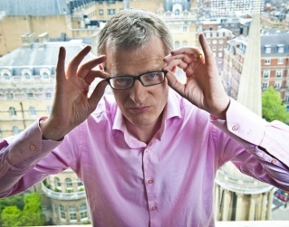 Jeremy Vine in a pink shirt, adjusting his glasses