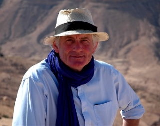Dan Cruickshank sits in front of mountains, wearing a blue shirt and a straw hat