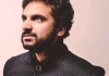 Nish Kumar wearing a black jacket standing against a pale pink background.