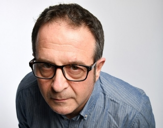 A man wearing a blue, striped shirt and black rimmed glasses leans towards the camera