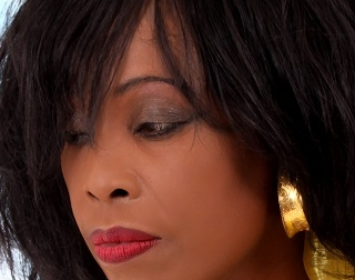 Singer Ruby Turner wears gold earrings and red lipstick and looks away from the camera