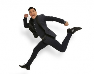 Comedian Russell Kane jumps through the air wearing a dark suit.