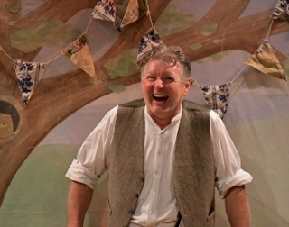 A performer in a brown waistcoat and white shirt stands in front of a set containing a tree and bunting