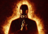 Comedian Romesh Ranganathan wears black and looks down, silhouetted against a bright, flaming background.