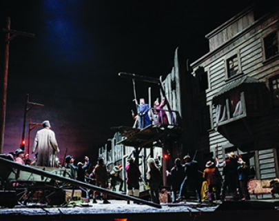 A dark American Western setting, with a crowd looking up towards a gallows platform