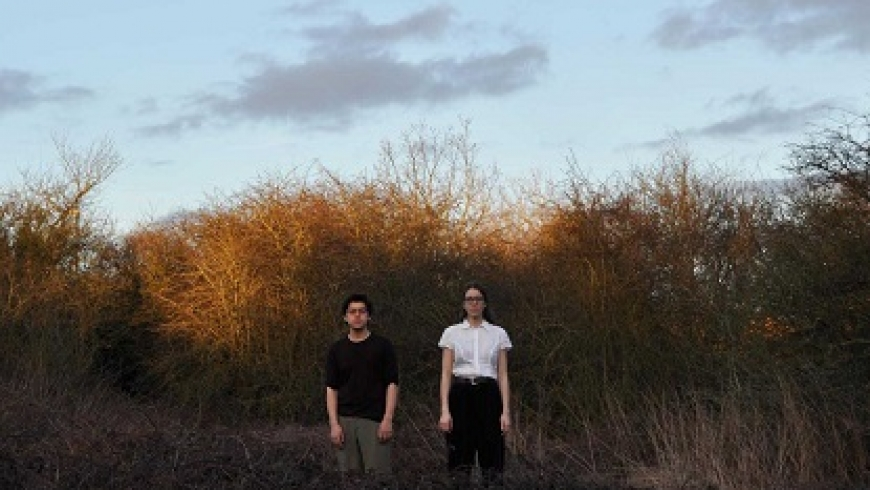 Two people stand in a field of tall, sunlit grass