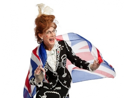 An elderly woman with stained teeth, bird's nest red hair and glasses smiles, whilst wearing a black embroidered jacket and a Union Jack flag.