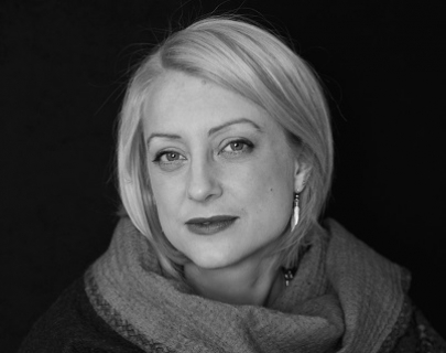 Black and white. A woman with a blonde bob wears a big scarf and long earrings and looks at the camera.