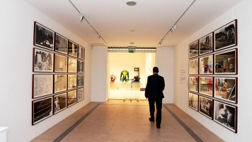 A man walks through the corridor leading to the Journeys With 'The waste Land' exhibition.